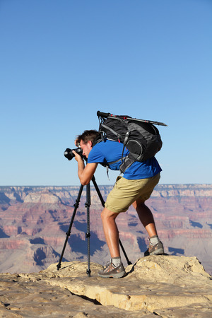 Nature landscape photographer in Grand Canyon taking picture photos with SLR camera and tripod during hike on south rim. Young man hiker enjoying landscape in Grand Canyon, Arizona, USA. photo