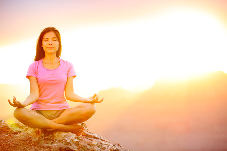 Yoga woman meditating at sunset in Grand Canyon. Female model meditating in serene harmony in lotus position. Healthy wellness lifestyle image with multicultural young woman. From Grand Canyon, USA. Stock Photo