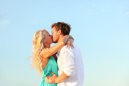 Kissing romantic couple in love happy embracing giving kiss outdoors. Young lovers man and woman in their 20s. photo