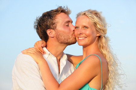 Kissing romantic couple in love smiling happy embracing in kiss outdoors. Young lovers man and woman in their 20s. photo
