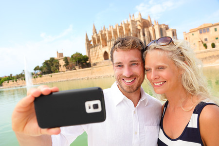Happy couple dating taking selfie photo with smartphone camera on Mallorca in front of La Seu, Palma Cathedral. Young couple on Majorca vacation holiday. Image from Mallorca, Balearic Islands, Spain. photo