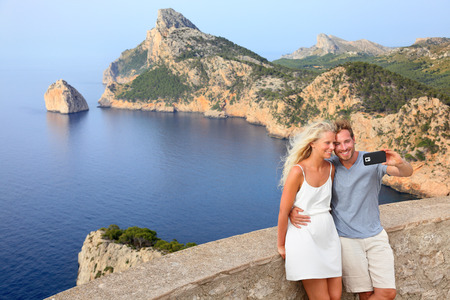 majorca: Couple taking selfie photo with smartphone on Cap de Formentor on Mallorca. Young couple on Majorca vacation holiday travel. Image from Mallorca, Balearic Islands, Spain.