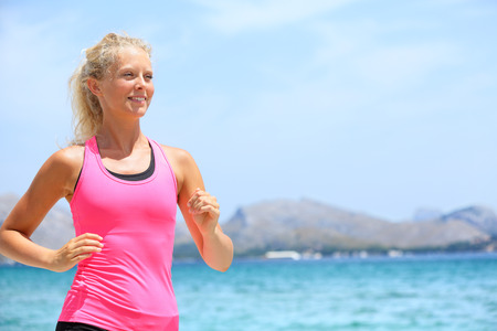 Running woman runner. Portrait of sport fitness girl jogging exercising outside on beach living healthy lifestyle enjoying outdoor activity. Blonde fitness model in her 20s. photo