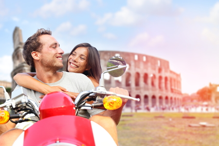 Italië Rome paar op scooter door Colosseum. Romantische gelukkige geliefden rijden scooter op huwelijksreis plezier in de voorkant van Coliseum. Liefde en reizen concept met multiraciale paar.