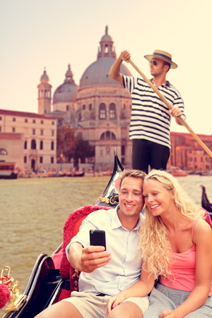 grande: Couple in Venice doing Gondola ride on canal grande taking selfie self portrait using smartphone camera. Happy young romantic couple traveling in Italy, Europe on vacation holidays.
