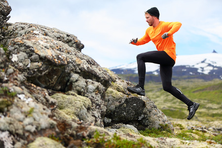 Hombre del deporte que se ejecuta en cruz carrera trail país. Fit entrenamiento físico corredor masculino y salto al aire libre en el hermoso paisaje de montaña con Snæfellsjökull, Snaefellsnes, Islandia. Foto de archivo