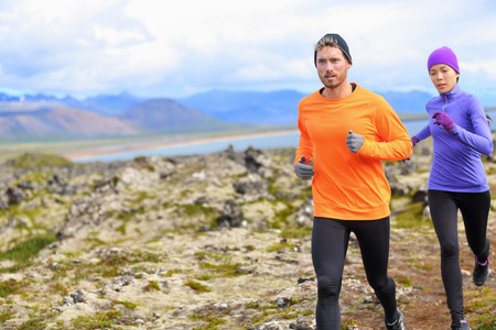 crosscountry: Trail runner man and woman running cross-country run training outside for marathon. Jogging male athlete working out as part of healthy lifestyle. Image from Snaefellsnes, Iceland.