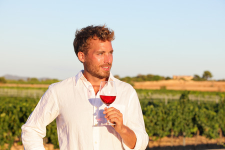 enjoy: Winemaker man drinking rose or red wine at vineyard from wine glass outdoors.