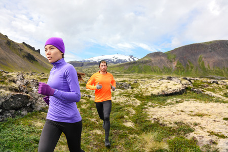 Trail running people in cross country run. Woman and man runners training jogging outdoors in beautiful mountain nature landscape on Snaefellsnes, Iceland. photo