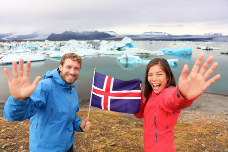 Icelandic flag - tourists on Jokulsarlon, Iceland on travel. Tourist couple happy holding showing Icelandic flag in front of the glacial lake  glacier lagoon.