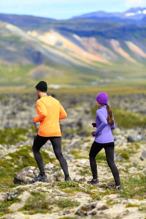 running pants: Running sport. Runners on cross country trail outdoors working out for marathon. Fit young fitness model man and asian woman training together outside in nature landscape on Snaefellsnes, Iceland. Stock Photo