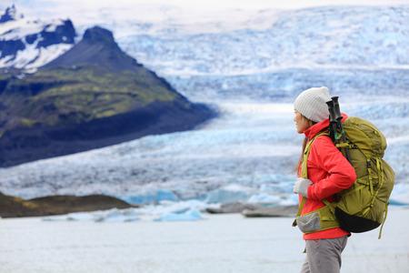 fjallsarlon: Adventure hiking woman by glacier on Iceland. Hiker trekking walking by glacial lagoon  lake of Fjallsarlon, Vatna glacier, Vatnajokull National Park. Young woman visiting Icelandic nature landscape.