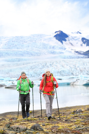 fjallsarlon: Adventure hikers travel people walking with hiking poles on Iceland by glacier and glacial lagoon  lake of Fjallsarlon, Vatna glacier, Vatnajokull National Park. Couple visiting Icelandic nature.