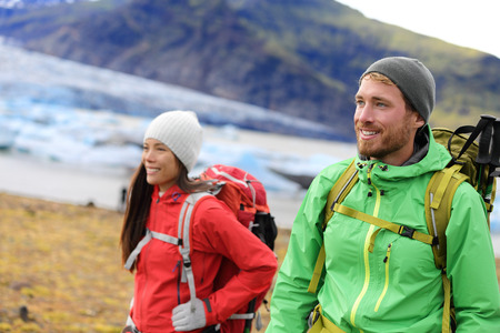 fjallsarlon: Hiking adventure travel people living active healthy lifestyle wearing jackets and backpacks on Iceland by glacier and glacial lagoon  lake of Fjallsarlon, Vatna glacier, Vatnajokull National Park. Stock Photo