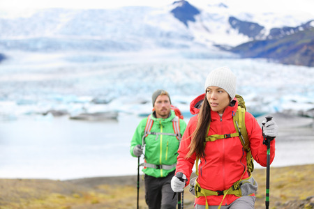 fjallsarlon: Adventure hiking people by glacier on Iceland walking with hiking poles by glacial lagoon  lake of Fjallsarlon, Vatna glacier, Vatnajokull National Park. Couple visiting Icelandic nature. Stock Photo