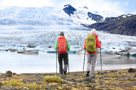 fjallsarlon: Hikers - people on adventure travel on Iceland. Hiking man man woman walking to glacier and glacial lagoon  lake of Fjallsarlon, Vatna glacier, Vatnajokull National Park. Couple in active lifestyle.