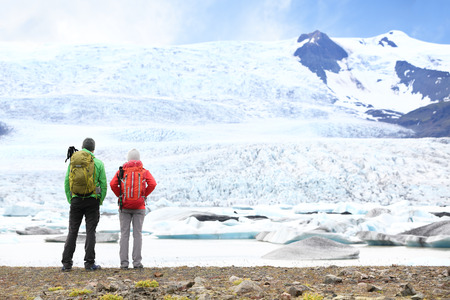 fjallsarlon: Hiking adventure travel people on Iceland. Hikers looking at glacier and glacial lagoon  lake of Fjallsarlon, Vatna glacier, Vatnajokull National Park. Couple visiting Icelandic nature landscape.