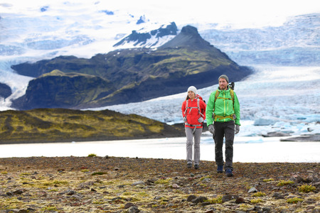 fjallsarlon: Adventure hiking travel couple trekking on Iceland. People by glacier and glacial lagoon  lake of Fjallsarlon, Vatna glacier, Vatnajokull National Park. Couple visiting Icelandic nature landscape.