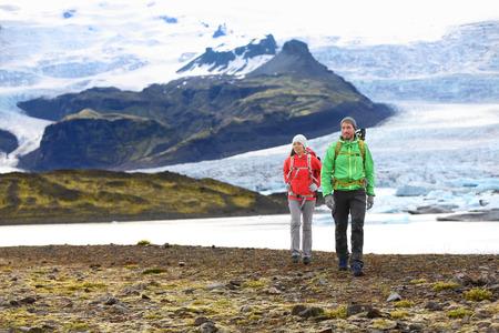 fjallsarlon: Adventure hiking travel couple trekking on Iceland. People by glacier and glacial lagoon  lake of Fjallsarlon, Vatna glacier, Vatnajokull National Park. Couple visiting Icelandic nature landscape.