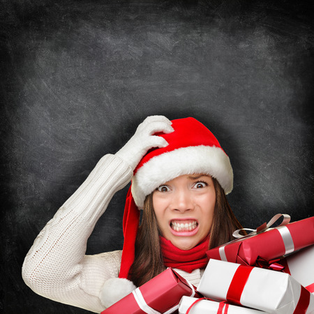 stress: Christmas holiday stress. Stressed woman shopping for gifts holding christmas presents wearing red santa hat looking angry and distressed with funny expression on blackboard background.