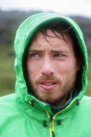 slicker: Rain jacket - man outdoors on rainy day in rain jacket. Portrait of male model wearing green shell jacket outside living outdoor lifestyle.