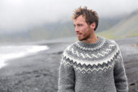 Handsome man walking black sand beach on Iceland wearing Icelandic sweater. Good looking male model looking pensive at ocean sea. Stock Photo