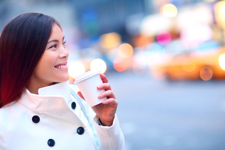 drinks: Professional young urban casual business woman in New York City Manhattan drinking coffee walking in street wearing coat downtown with yellow taxi cabs in background.