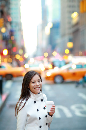 Young casual urban professional business woman in New York City Manhattan drinking coffee walking in street wearing coat downtown with yellow taxi cabs in background. photo