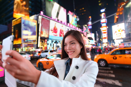 travellers: Happy woman tourist taking photo picture with tablet in New York City, Manhattan, Times Square. Girl traveler taking selfie joyful and happy smiling. Multiethnic Asian Caucasian woman in her 20s.