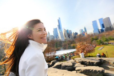 late fall: Woman in Central park, New York City in late fall early winter with skating rink in background. Candid smiling multi-ethnic girl on Manhattan, USA. Stock Photo