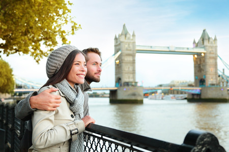 traveller: Happy couple by Tower Bridge, River Thames. Romantic young couple enjoying view during travel. Asian woman, Caucasian man in London, England, United Kingdom