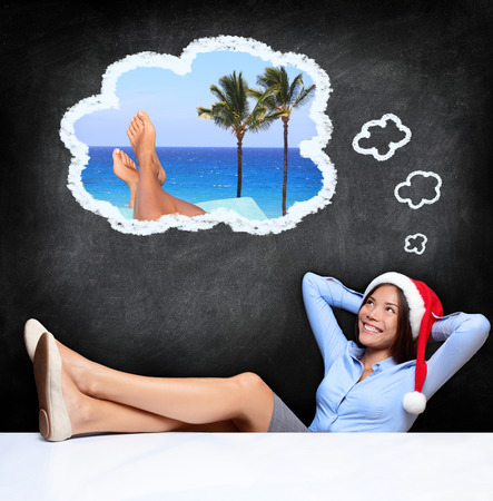 wish desire: Young woman dreaming about tropical holidays while sitting with the feet over the desk and wearing a Santa hat