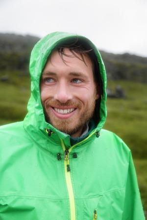 slicker: Rain jacket - man smiling outdoors on rainy day. Portrait of male model wearing green rain jackets outside living outdoor lifestyle.