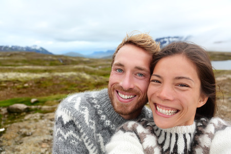 Iceland couple selfie wearing Icelandic sweaters in beautiful nature landscape on Iceland. Woman and man model in typical Icelandic sweater. Multiracial couple, Asian woman, Caucasian man. photo