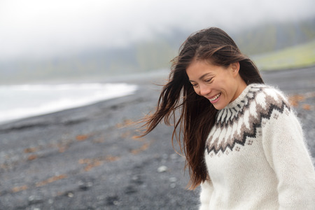 walking down: Cute woman walking on black sand beach on Iceland wearing Icelandic sweater. Pretty beautiful adorable multiracial Asian  Caucasian female model looking shy down by the ocean sea smiling happy. Stock Photo