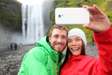 Selfie couple taking smartphone picture of waterfall outdoors in front of Skogafoss on Iceland. Couple visiting famous tourist attractions and landmarks in Icelandic nature landscape on Golden Circle. photo