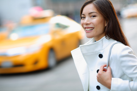 New York City Manhattan woman walking in street wearing coat downtown with yellow taxi cabs in background. Multiracial young urban professional in USA.