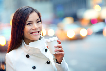 Young casual urban professional woman in New York City Manhattan drinking coffee walking in street wearing coat downtown with yellow taxi cabs in background. Female business woman. photo
