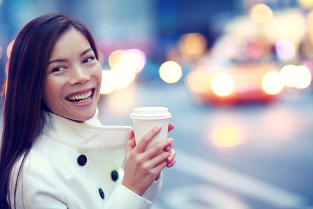 Professional young urban casual business woman happy in New York City Manhattan drinking coffee walking in street wearing coat downtown with yellow taxi cabs in background. Stock Photo