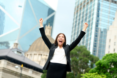 arms raised: Business success - celebrating businesswoman in Hong Kong cheering business goals with arms raised up as winner. Young mixed race Chinese Asian  Caucasian female professional in Hong Kong central.