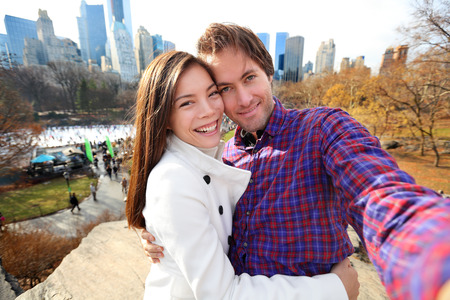 winter photos: Dating young couple happy in love taking self-portrait selfie photo in Central Park, New York City in late fall early winter with skating rink in background. Tourists having fun date, Manhattan, USA.