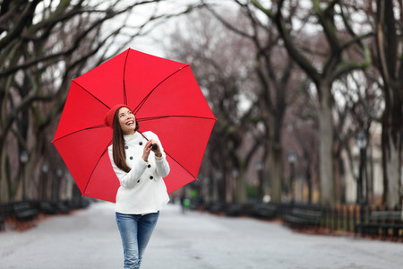 Woman with red umbrella walking in park in fall. Happy smiling multiracial girl walking cheerful with red umbrella in Central Park, Manhattan, New York City, USA. Stock Photo