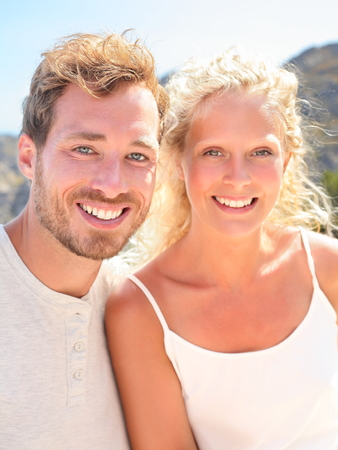 Young couple portrait. Beautiful young people smiling happy looking at camera in outdoors portrait. Candid real couple on sunny summer day. Woman and man in their 20s. photo