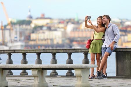 Europa reizen. Romantisch paar toeristen in Stockholm nemen selfie foto plezier genieten van uitzicht op de skyline en de rivier door Stockholms Stadhuis, Zweden.
