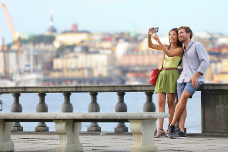 tourists: Europe travel. Romantic couple tourists in Stockholm taking selfie photo having fun enjoying skyline view and river by Stockholms City Hall, Sweden. Stock Photo