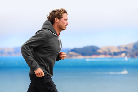 outfit: Athlete man running in sweatshirt hoodie in autumn fall by the water. Male runner training outdoors jogging in nature.