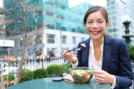 Business woman eating salad on lunch break in City Park living healthy lifestyle. Happy smiling multiracial young businesswoman, Bryant Park, Manhattan, New York City, USA