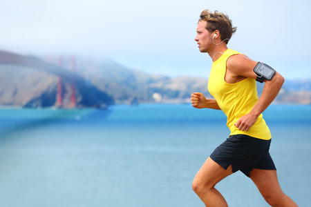 man: Athlete running man - male runner in San Francisco listening to music on smartphone. Sporty fit young man jogging by San Francisco Bay and Golden Gate Bridge. Jogger training with smart phone armband, Stock Photo