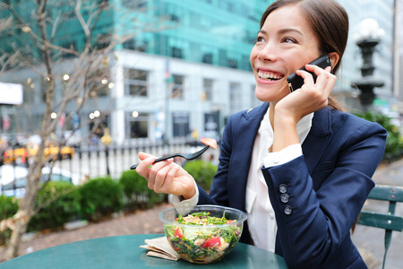 Young business woman talking on smartphone eating salad on lunch break in City Park living healthy lifestyle working on smart phone. Happy businesswoman, Bryant Park, manhattan, New York City, USA
