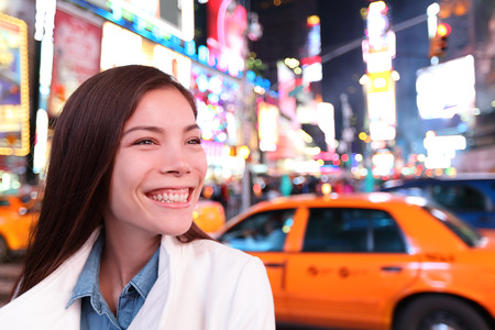 times square: Woman in New York City, Manhattan, Times Square at night. Smiling happy joyful Multiethnic Asian Caucasian young urban professional in her 20s.